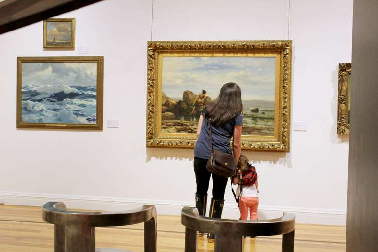 A parent and child view a painting in the galleries of the Berkshire Museum.