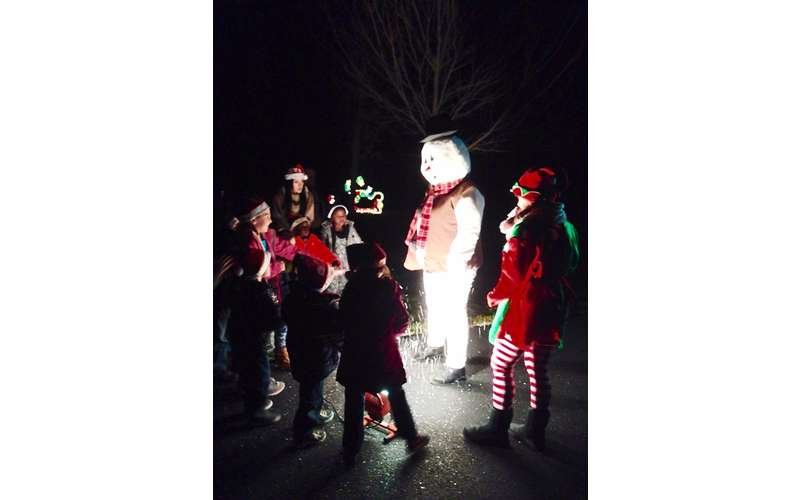 kids near person dressed as frosty the snowman