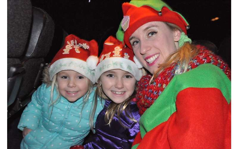 woman dressed as elf and two kids smiling for a photo