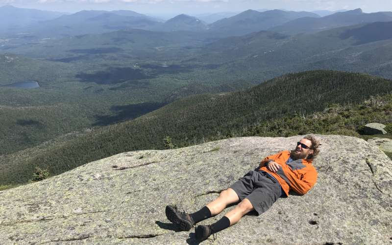 hiker laying on rocky summit