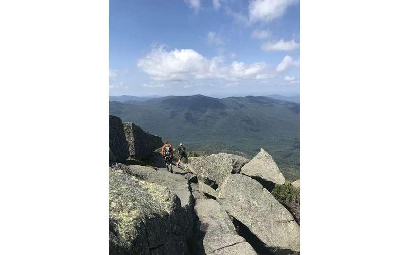 people walking on rocky area of mountain