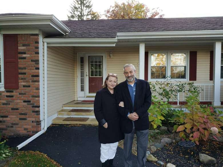 man and woman standing in front of a house