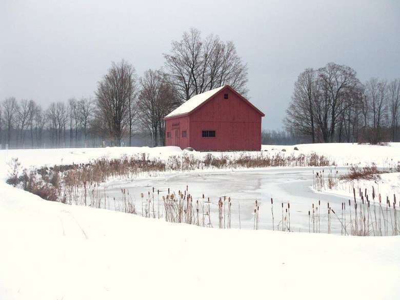 red barn surrounded by snow covered ground