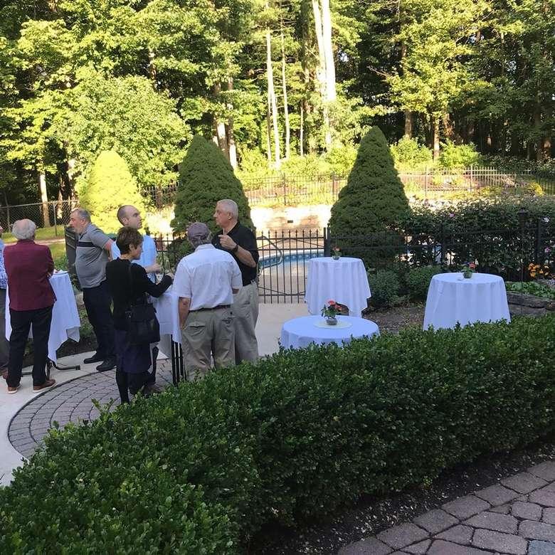 people outside in a garden area near tables
