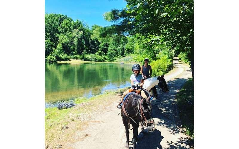 two horseback riders on a path near a lake