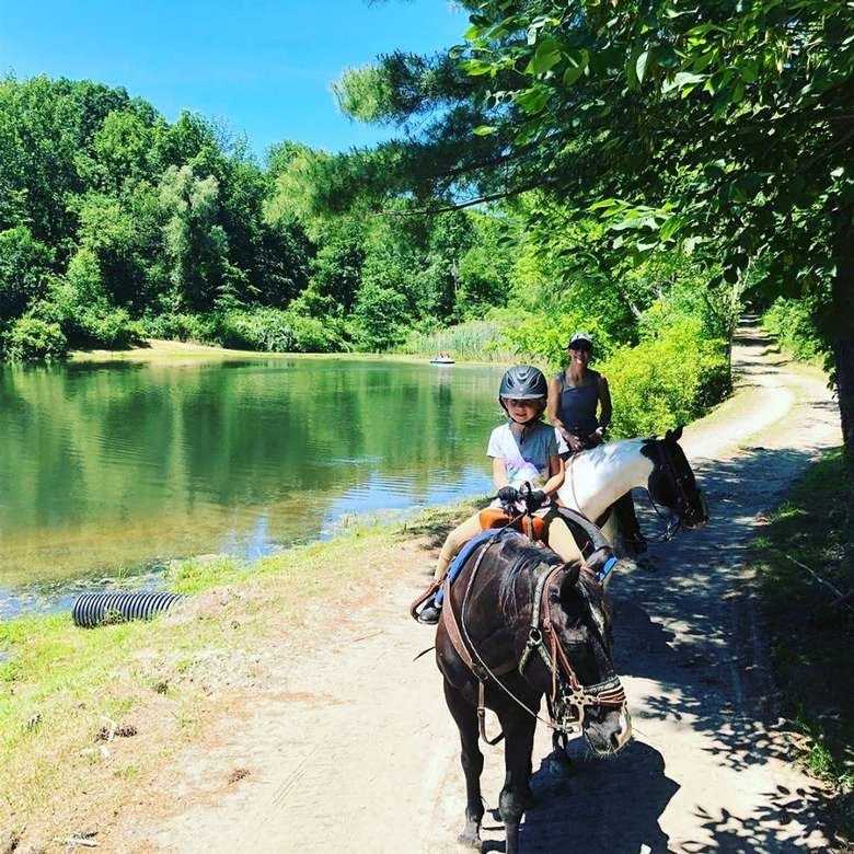 two horseback riders on a path near a lake