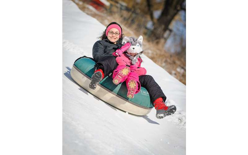 two people snow tubing together
