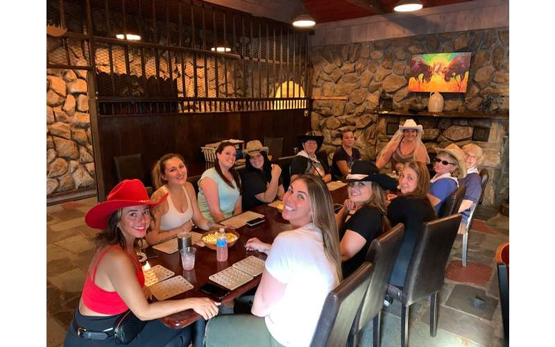 group of women at a western themed event in a room with stone walls