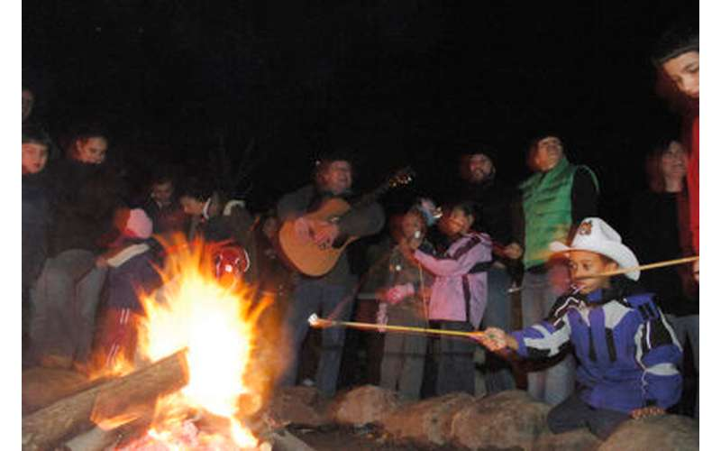 group of people sitting around a campfire at night