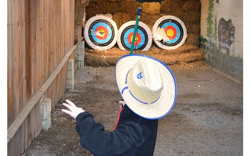 kid practicing archery with three targets
