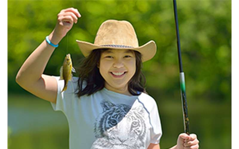 girl holding up a fishing pole and a fish