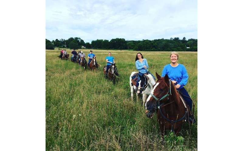 a line of people riding horses in a grassy field together