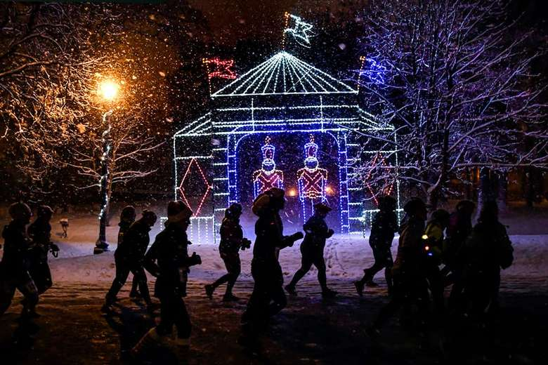 people running at night near holiday lights display