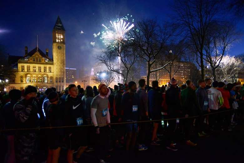 people lined up for a race at night with fireworks going off in the background