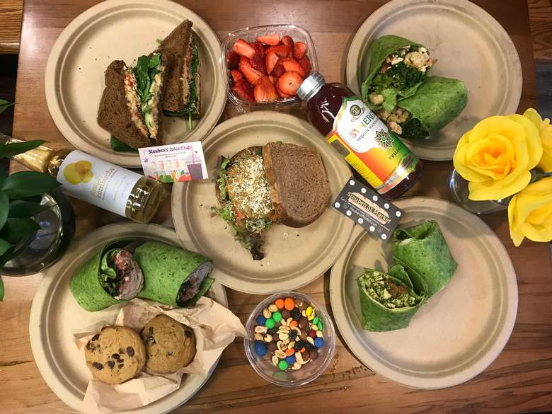 plates on a table with sandwiches, wraps, fruit, and bottles