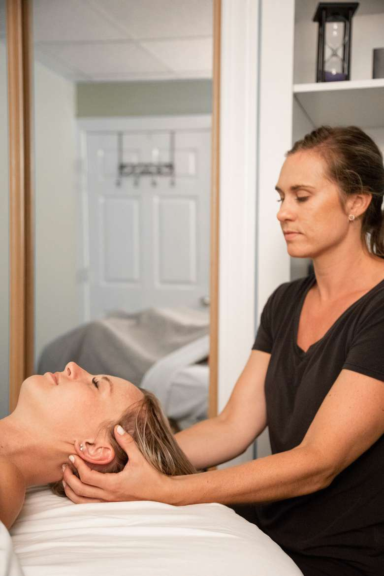 massage therapist holding woman's head from behind