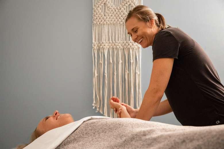 massage therapist holding woman's hand