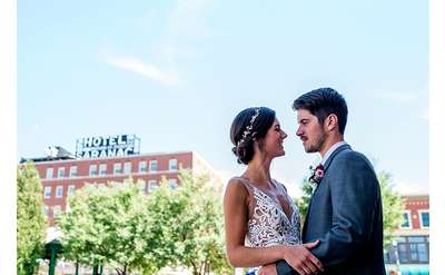 bride and groom with hotel in the background