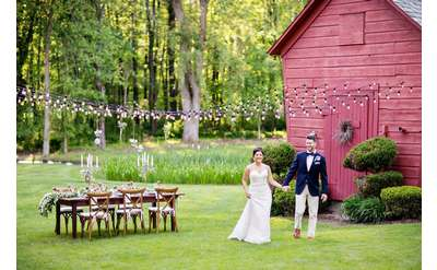 bride and groom holding hands by barn