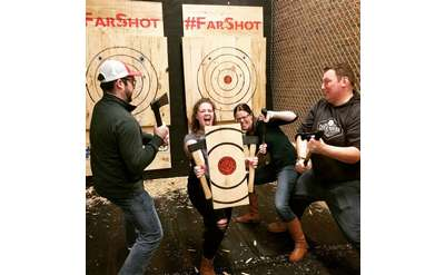 people at axe throwing place posing
