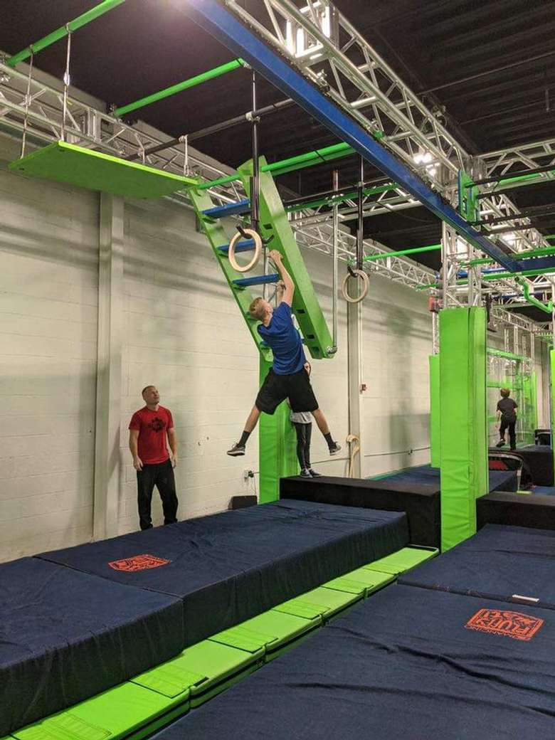 young man on hanging ladder obstacle in a gym