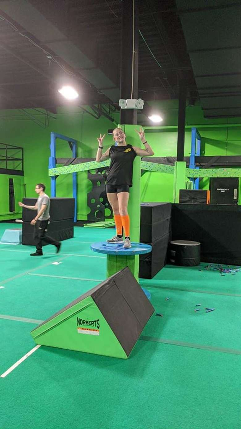 girl standing on a ninja obstacle in a gym