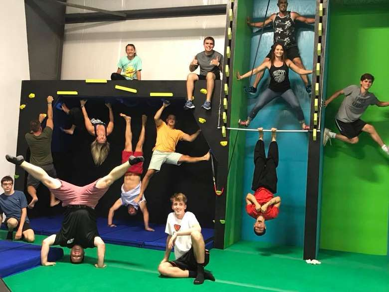 group of people on ninja fitness equipment