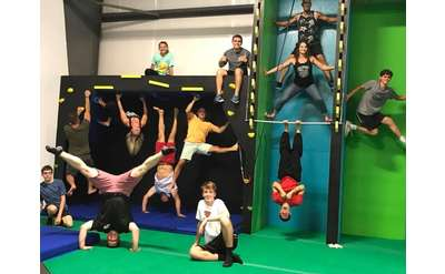 group of people on ninja obstacles in a gym