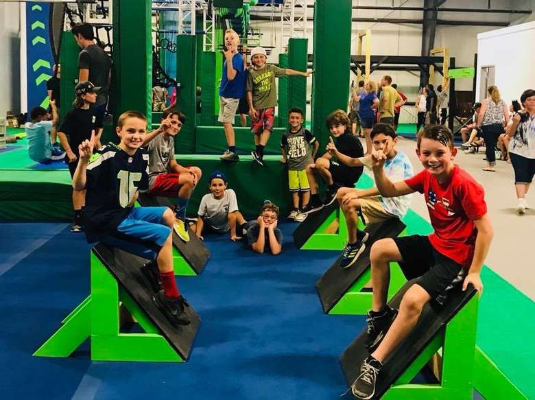 group of kids relaxing on step pieces in a gym