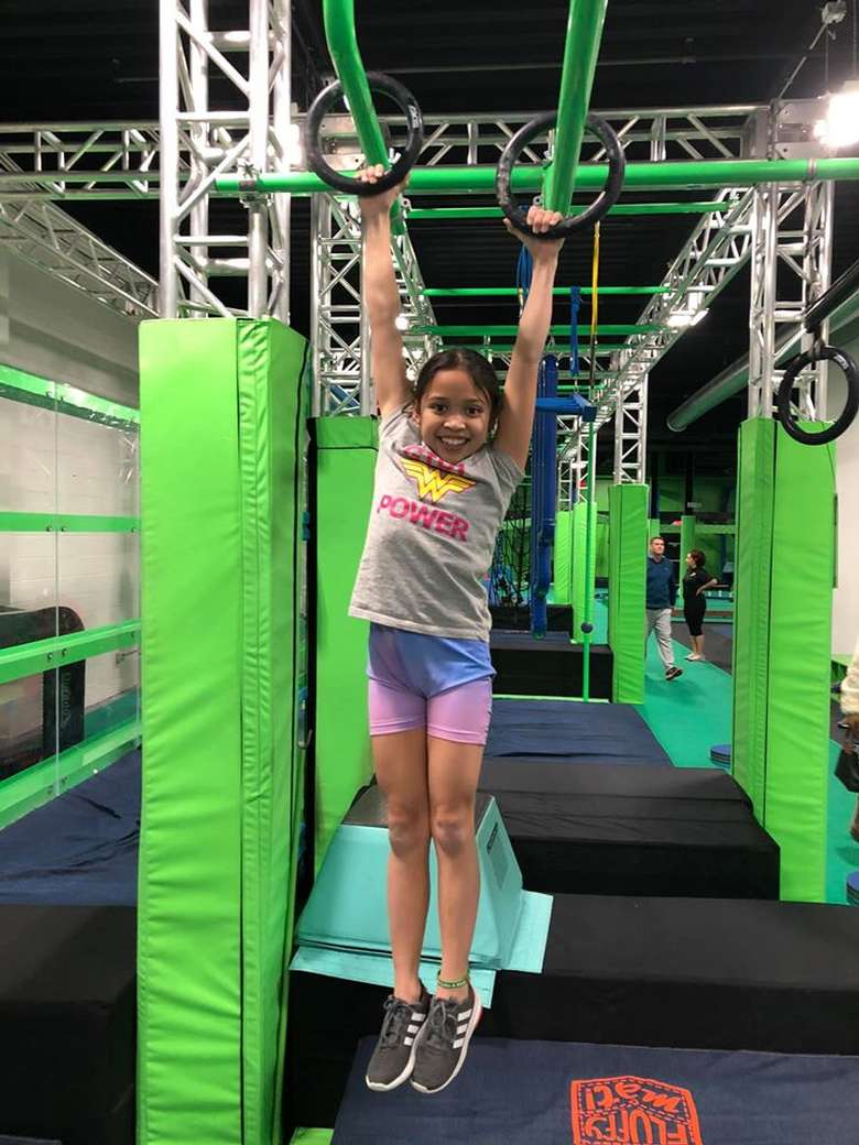 girl hanging onto rings in a gym