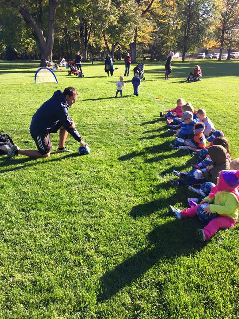 male instructor talking with kids on a soccer field