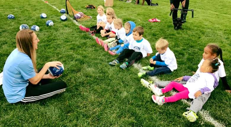 female instructor talking with kids on a soccer field