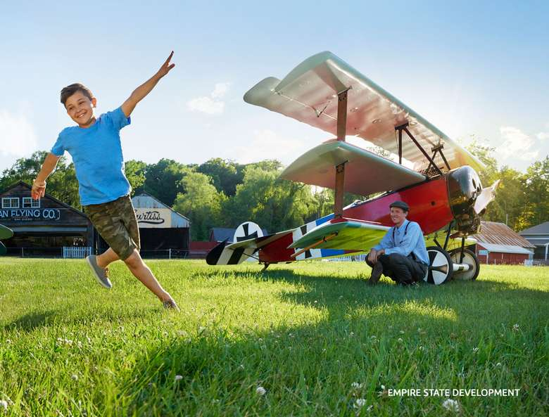 airplane on ground and a boy running on grass