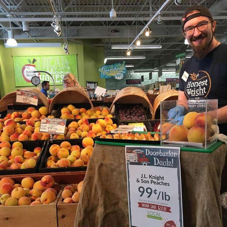 man standing near peaches
