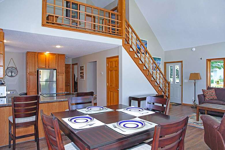 dining room table and living room with stairs leading up
