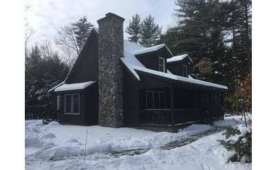 house with stone chimney with snow around