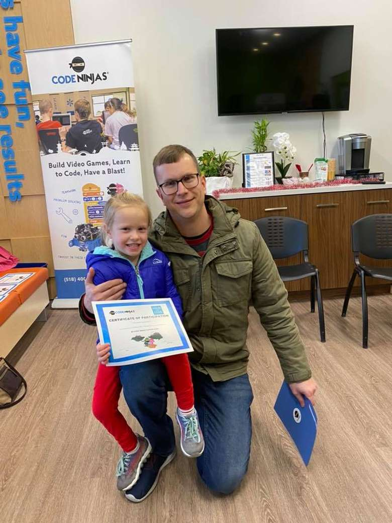 dad with daughter holding up certificate