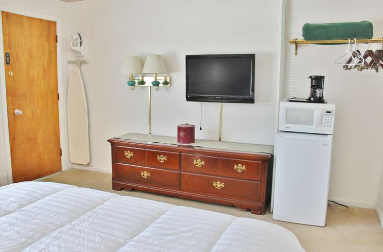 motel room with dresser, tv, and microwave