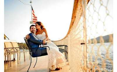bride and groom smiling on the bow of a boat