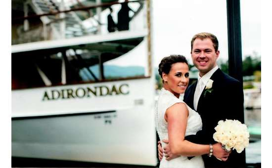 bride and groom posing in front of the adirondac boat