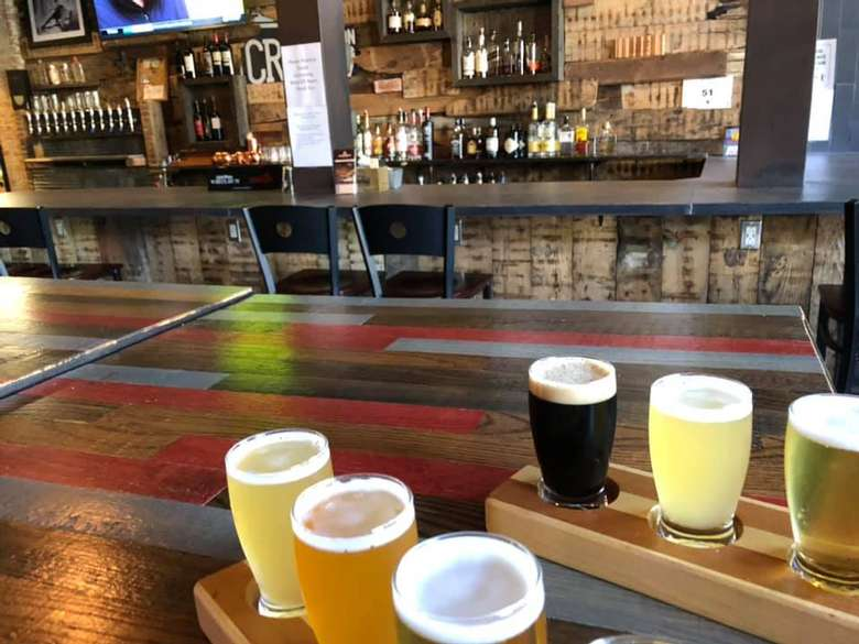 six beers on a wooden table with a bar in the background