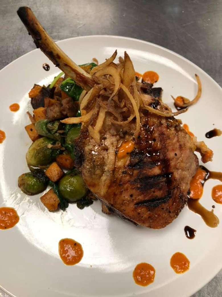 a bone in cut pork chop on a plate with brussels sprouts