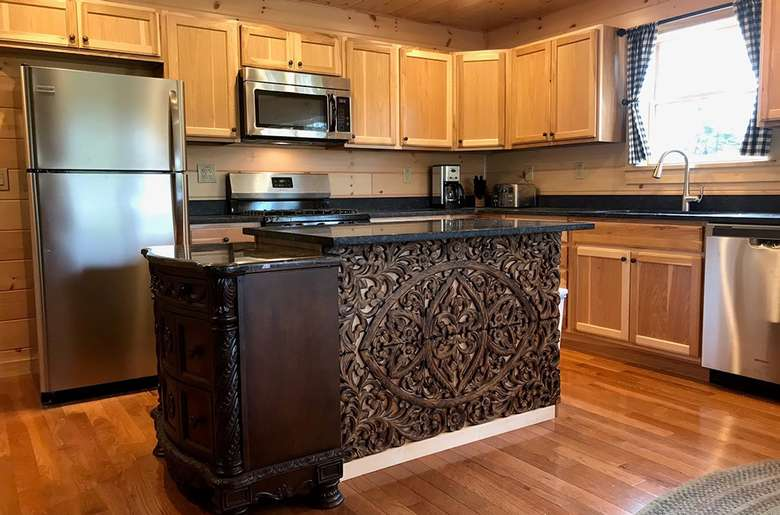 kitchen with a fridge, microwave, island counter, and sink