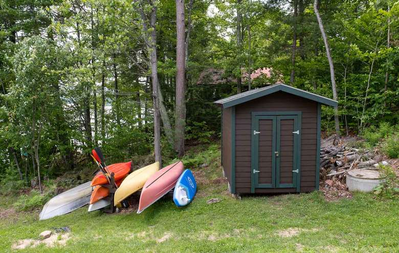 kayaks and boats next to a shed