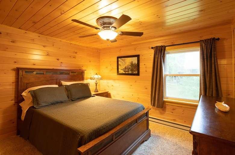 bed in bedroom, wood panel walls