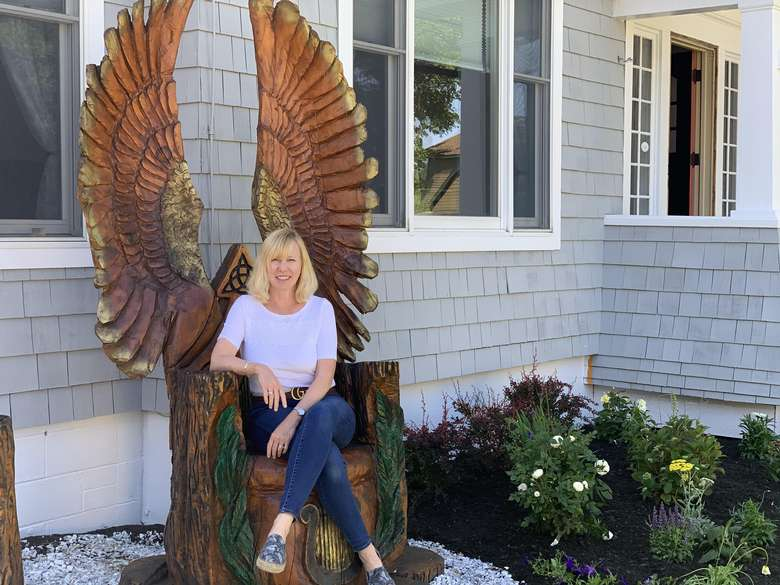 woman sitting in chair with wings