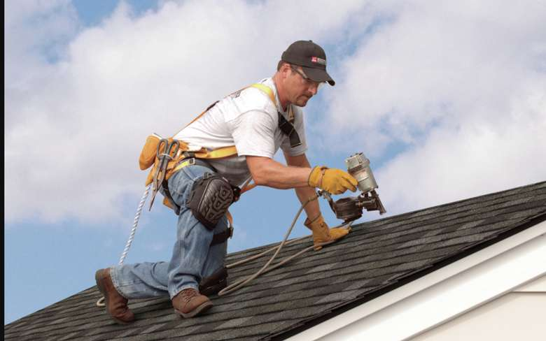 man using drill on roof