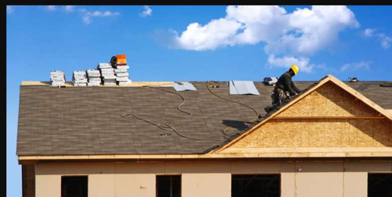 roofer working on the roof of a house under construction