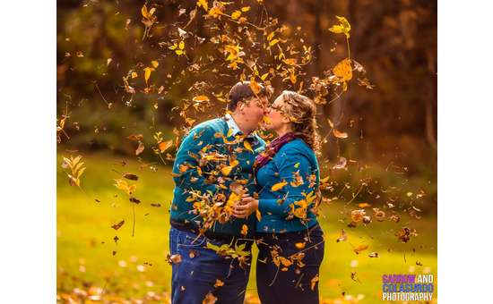couple kissing with leaves blowing around them