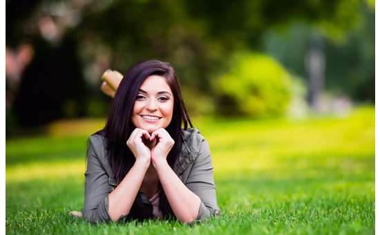 smiling woman posing on grass